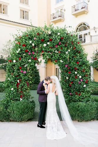 Bride and groom beneath floral arch