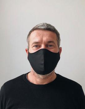 mann har på seg svart munnbind av bomull