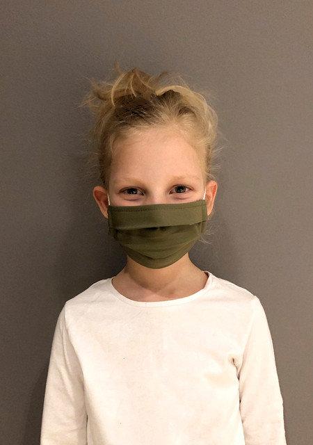barn har på seg grønt munnbind laget av bomull