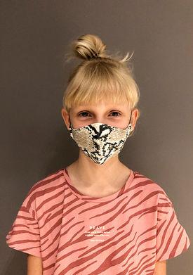 barn har på seg munnbind av bomull