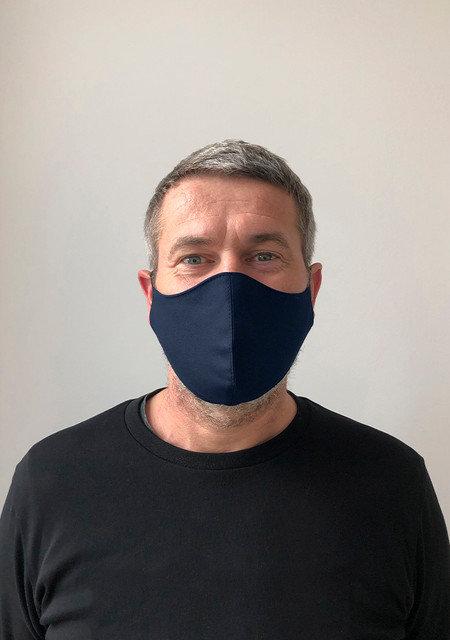 mann har på seg mørk blå munnbind laget av bomull