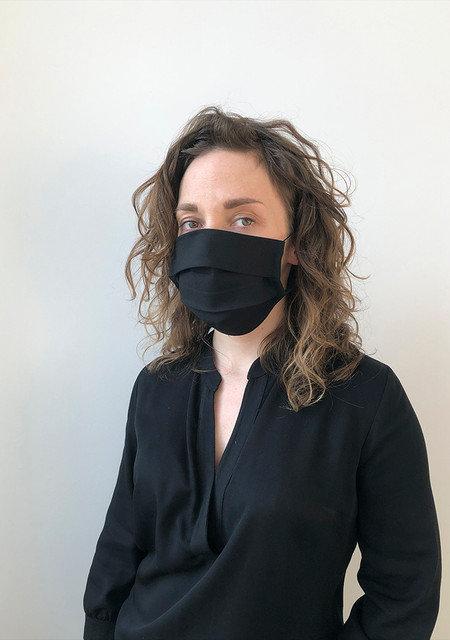 kvinne har på seg svart klassisk munnbind laget av bomull