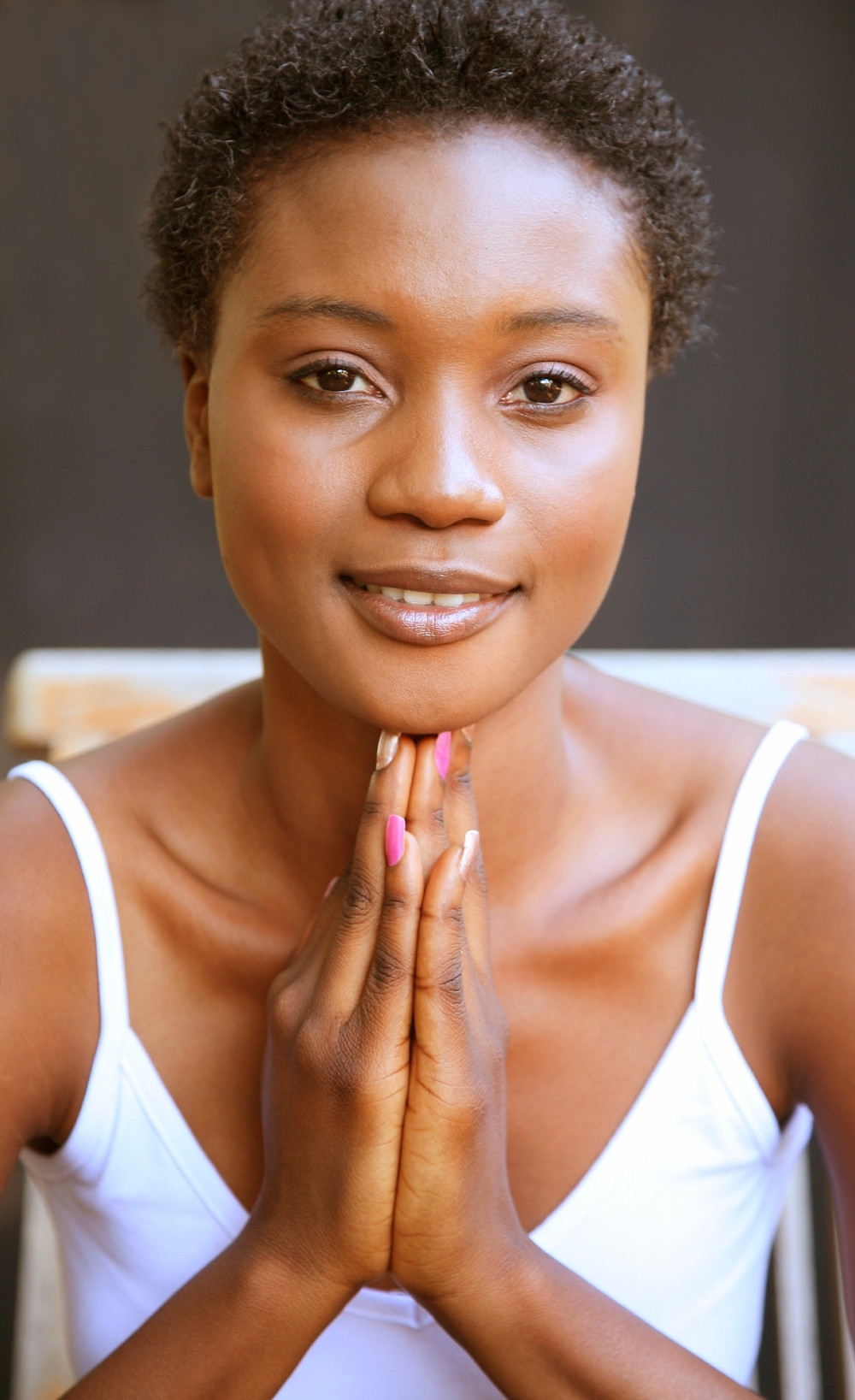 A young black woman, with closely cropped hair, looking serene, and having the palms of her hands together, finger tips touching her chin.