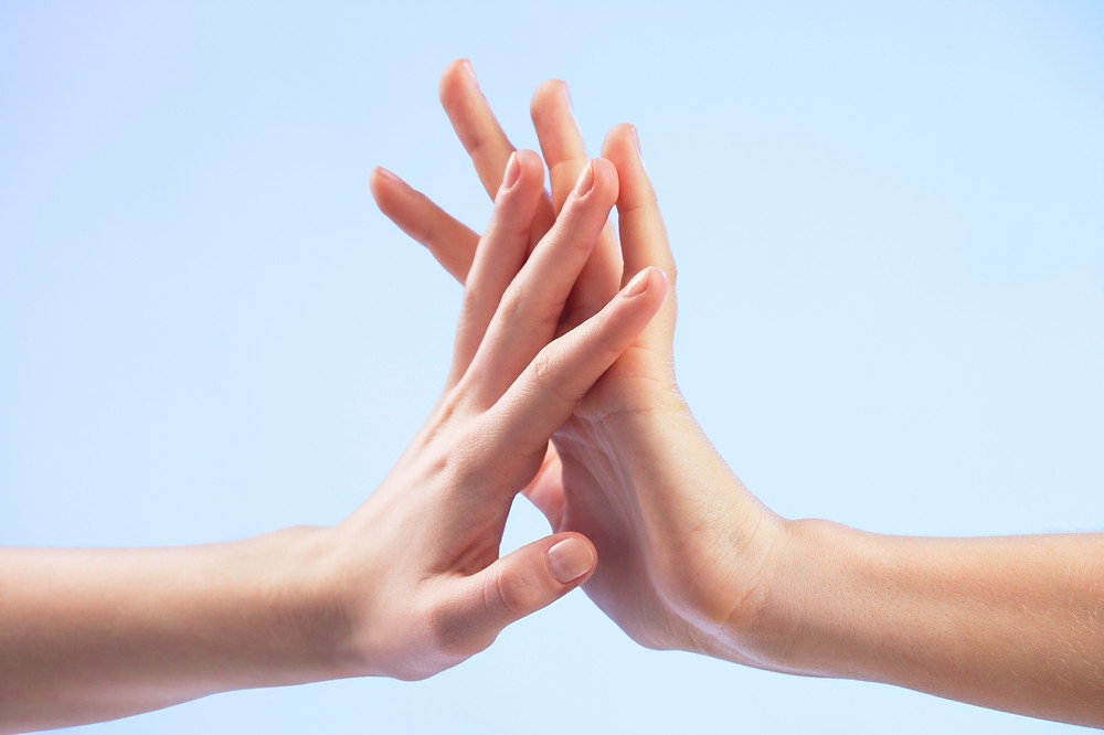Two hands, touching palms and fingers, in the middle of the frame.