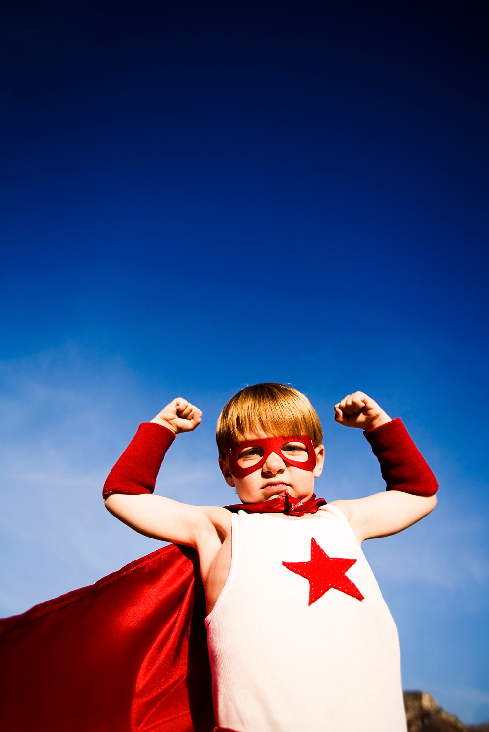 A young child in a red and white superhero outfit, with a cape, holding his arms in the air, flexing muscles.