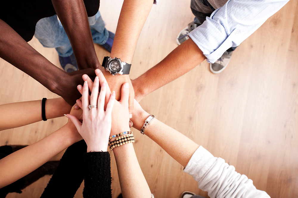 Looking down from above, hands extended on top of each other, representing various people and ethnicities.