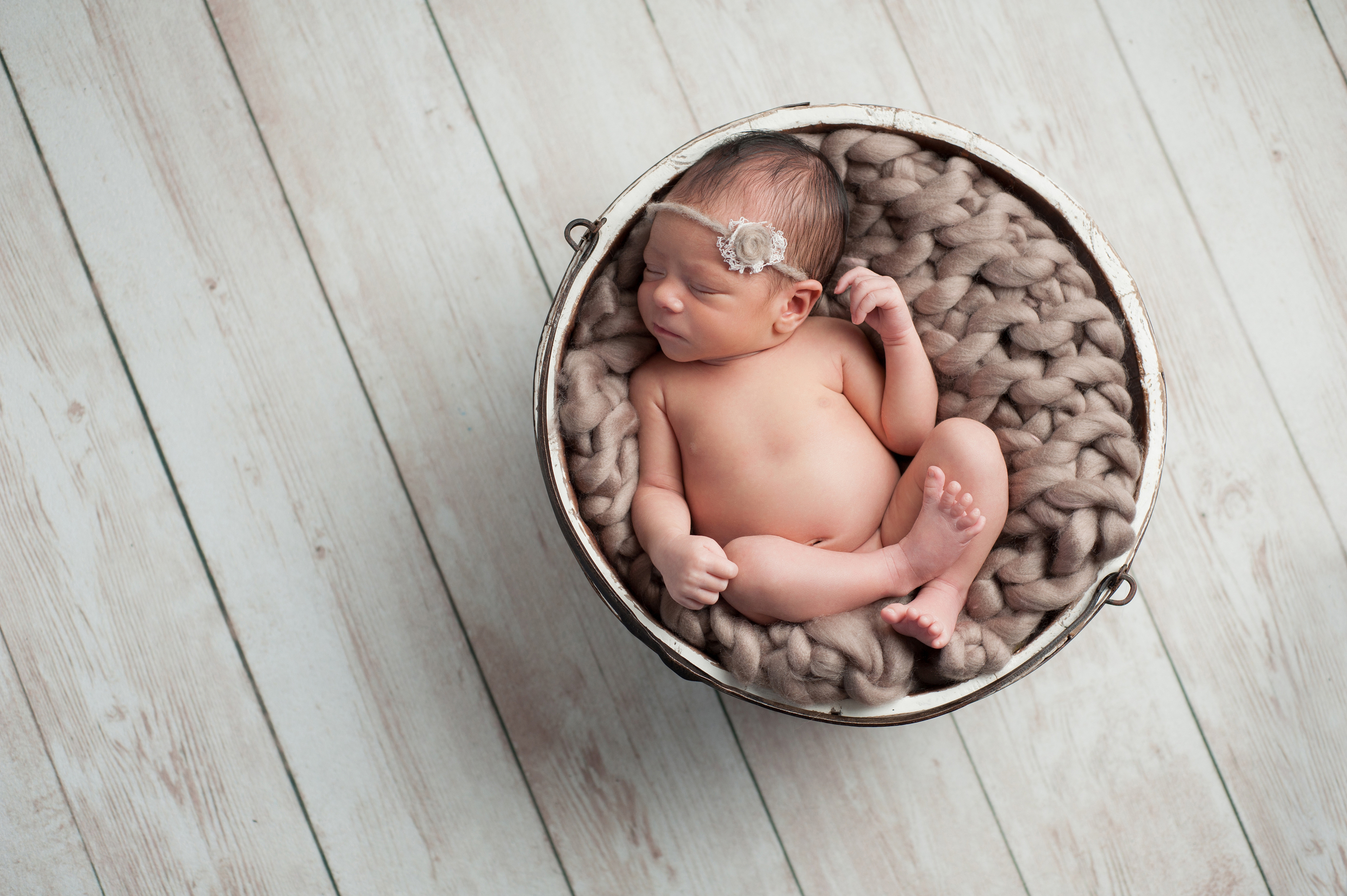 Newborn Girl Sleeping In Wooden Bowl