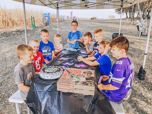 boys-having-fun-at-pumpkin-patch-birthday-party-party-tent-birthday-cake