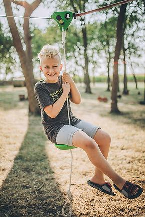 blond-boy-zip-line-through-trees