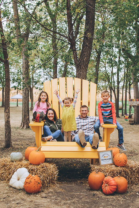 family-photo-gian-yellow-chair-happy-kids-proud-parents