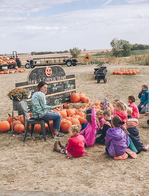 pumpkin-patch-field-trip-happy-engaging-children-orange-pumpkin-black-wagons