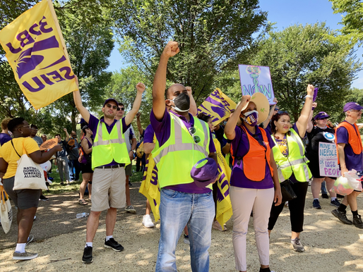At a recent labor rally Kristin supported. SEIU 32BJ members in foreground raise their fists and wave union flags.