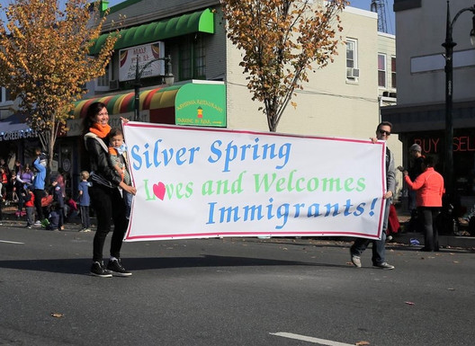 """Kristin carrying banner stating """"Silver Spring Loves And Welcomes Immigrants!"""" in parade"""