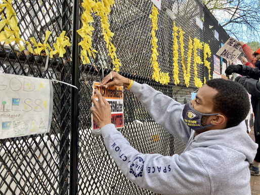"""TJ of local advocacy nonprofit Spaces In Action hangs a sign stating """"Black Voters Matters"""" on the fence in front of the White House."""