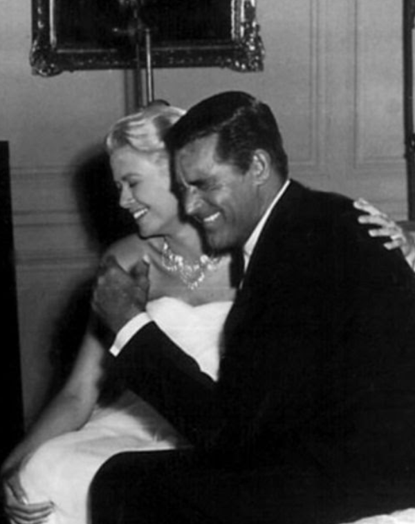 Grace Kelly on the left hugging and smiling Cary Grant on the right