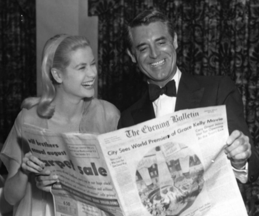 """During the 1955 Philadelphia film premiere, a headline of The Evening Bulletin proclaims """"City Sees World Premiere of Grace Kelly Movie"""" with Grace and Cary enjoying a hearty laugh."""
