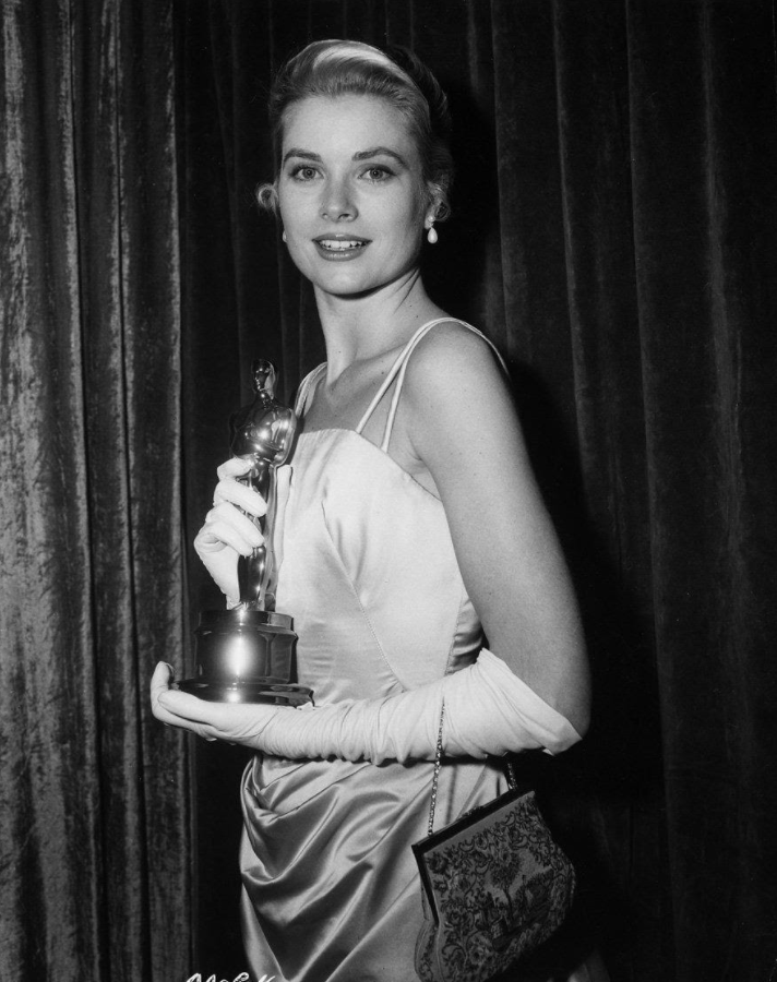 grace kelly holding her oscar award in her champagne blue gown