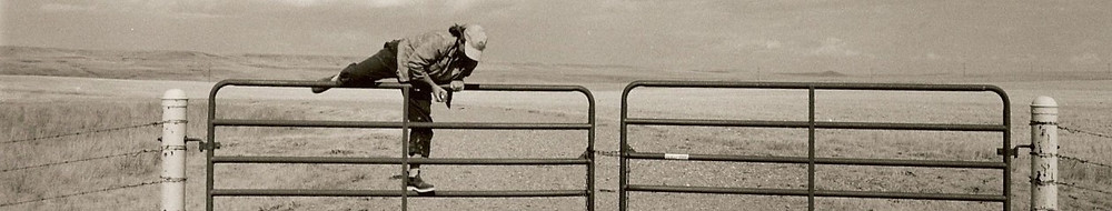 Frances climbing over a fence in Montana. Photo credit: Mary Randlett