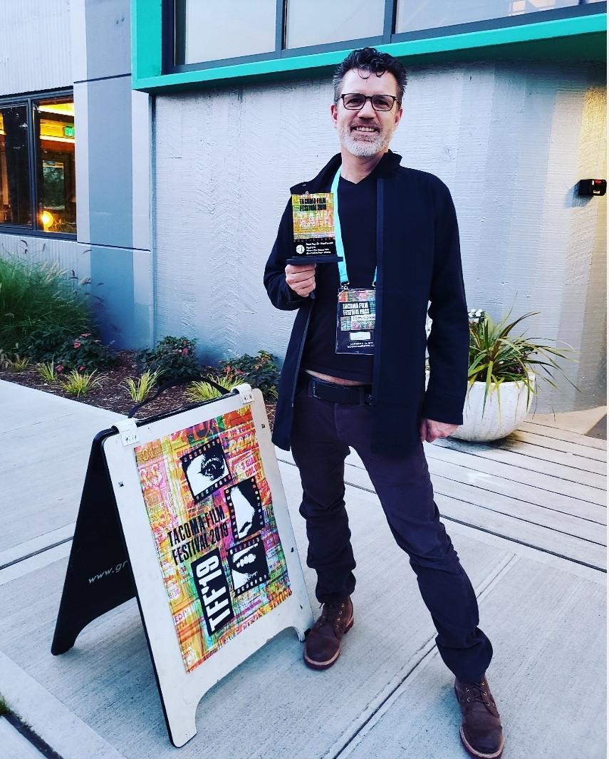 Director Ryan K. Adams holding award