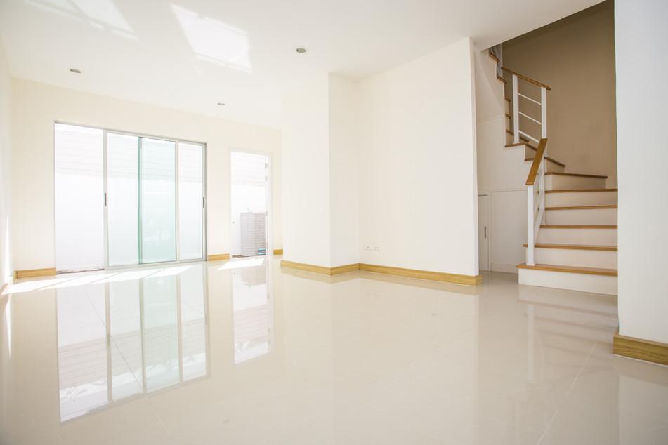 Il salone di Gabriele. Applicazione di Resina ERRELAB lucida colore bianco, battiscopa e rivestimento scala in Rovere naturale.