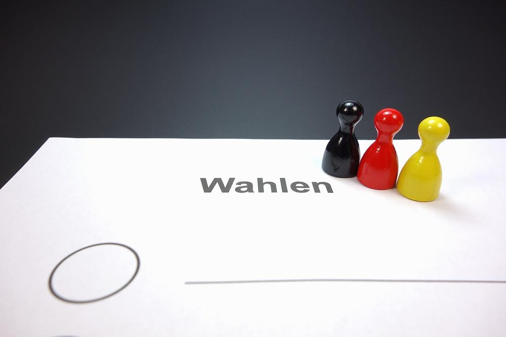 Das Bild zeigt einen Stimmzettel und drei Spielfiguren in den Farben schwarz, rot und gelb.