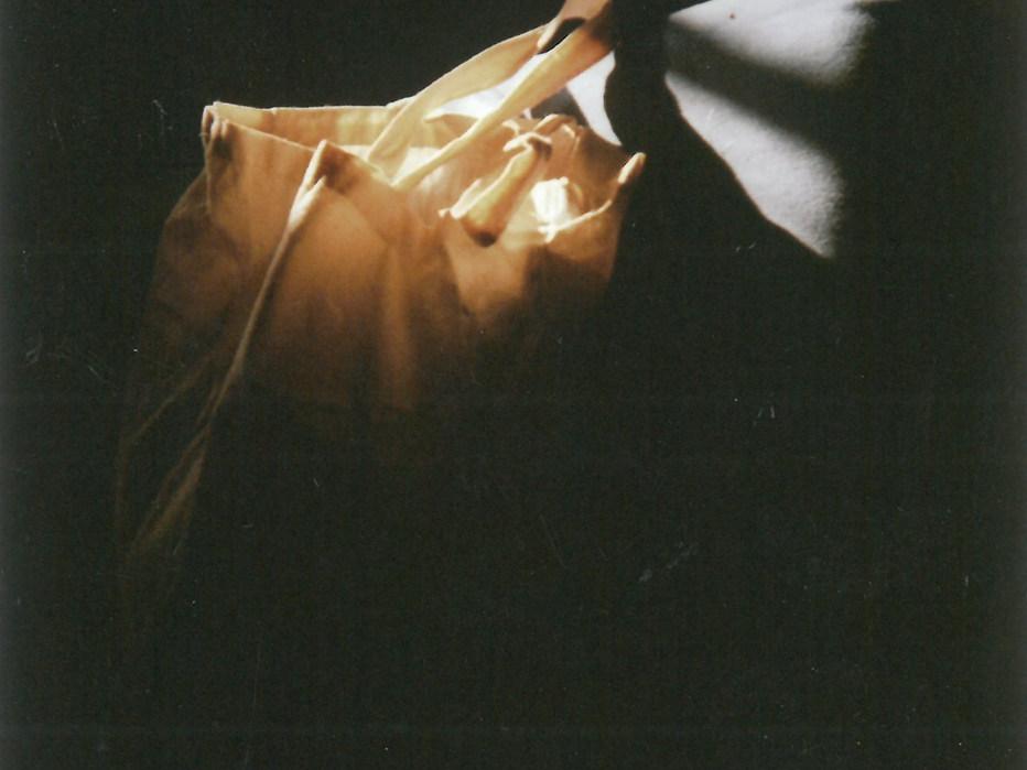 Zu sehen ist eine weiße Stofftasche die auf meinem Bett liegt. Das Bild fängt den alltäglichen Moment ein, wenn der letzte Sonnenstrahl des Tages mein Zimmer erleuchtet. Zufällig traf er genau die Tasche auf dem Bett.