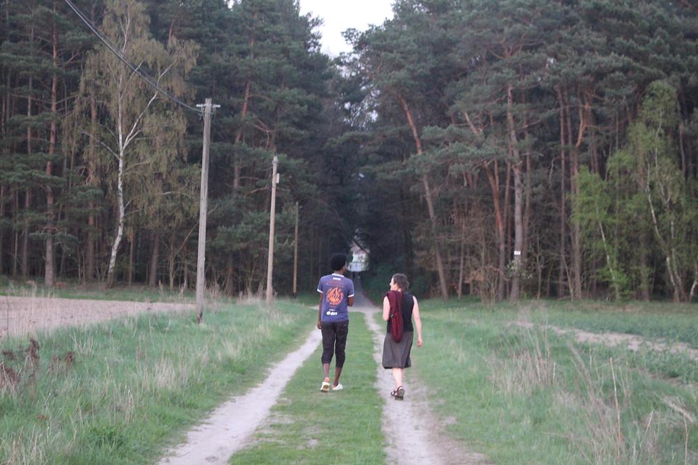 Zwei Menschen gehen auf einem Feldweg entlang und unterhalten sich.