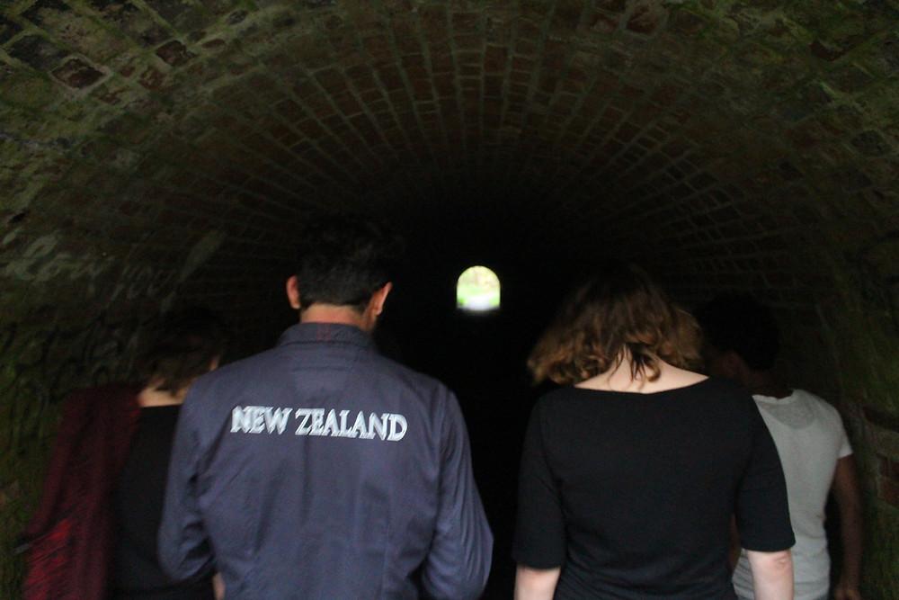 Eine Gruppe Menschen läuft durch einen unbelichteten Tunnel