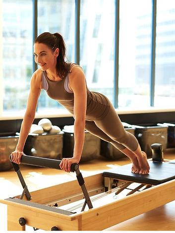 brunette-woman-practicing-pilates-in-stu