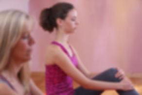 Zwei Frauen sitzen in Stille mit einem Bein angewinkelt. Esoterisches Yoga