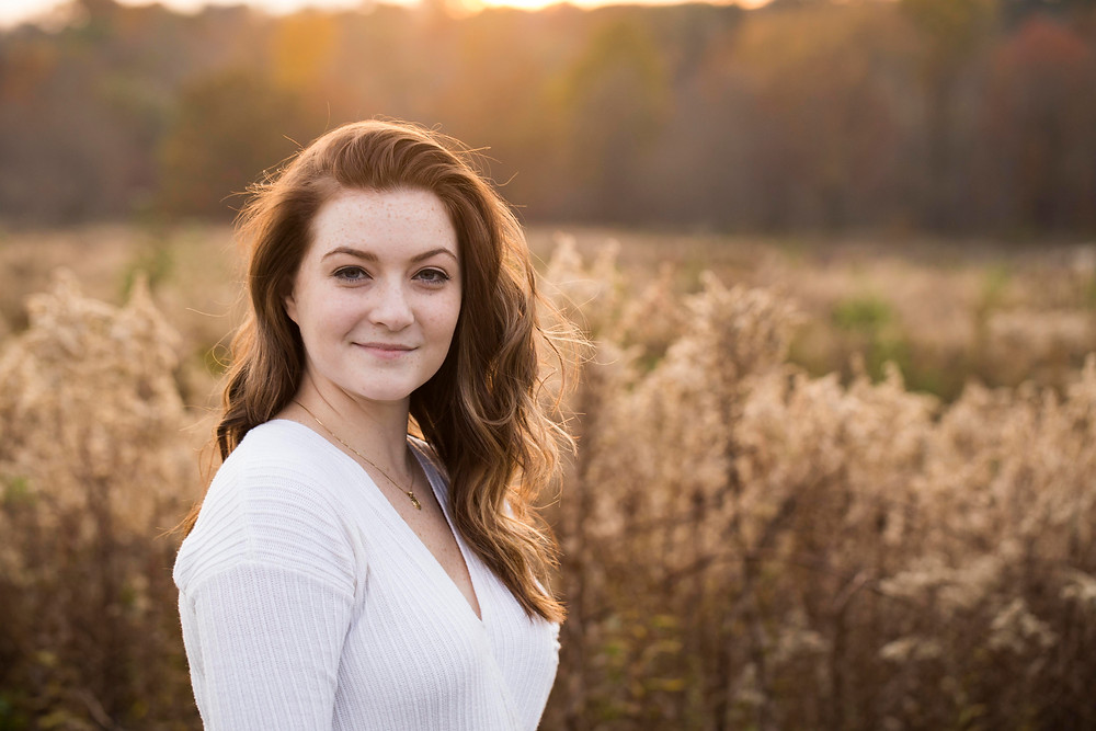 RAW photo of high school senior natural light portrait during golden hour in field of grass