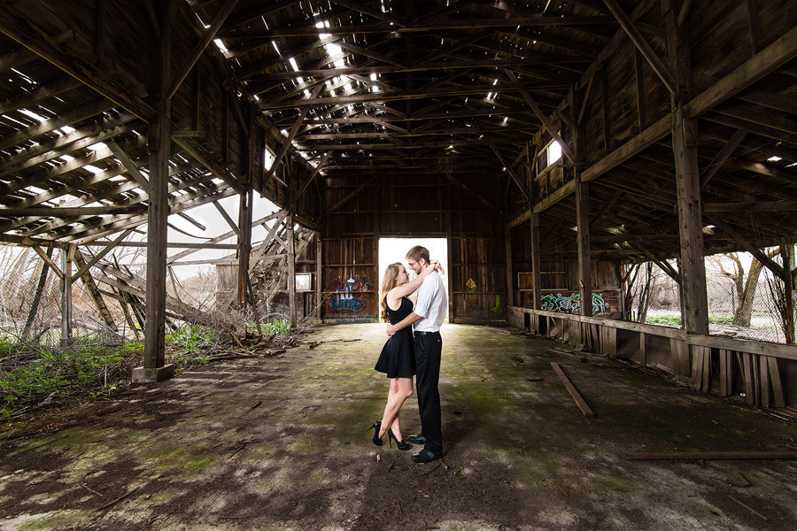 A wide angle engagement photo of a couple in an abandoned building.