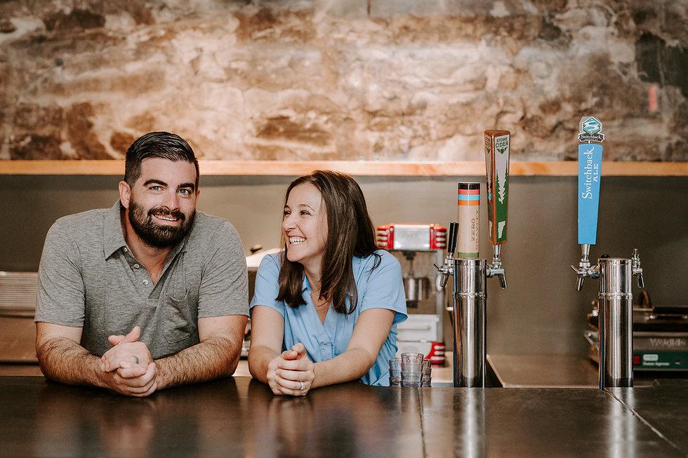 Nick and Lauren smiling behind bar.jpg