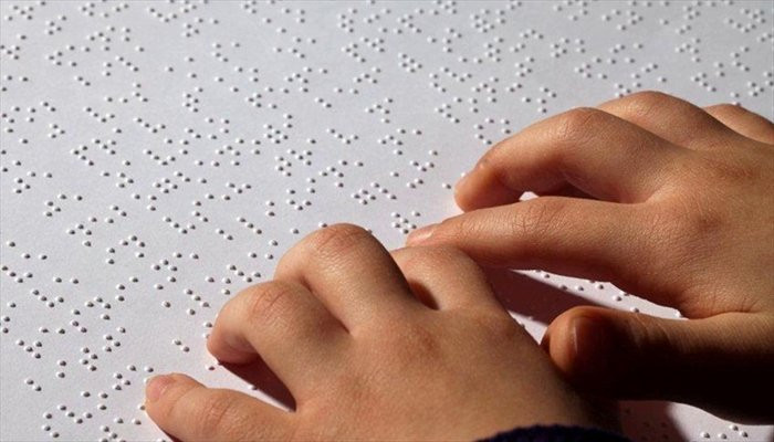 Two hands reading a braille text