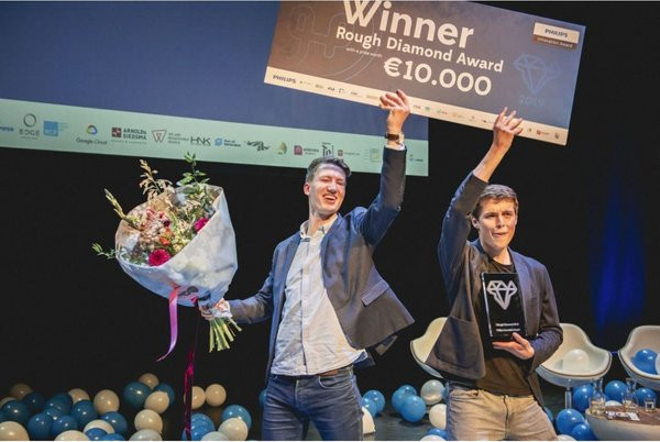Hable employees Freek and Tom celebrating and holding their rough diamond award of 10.000 euros in the air
