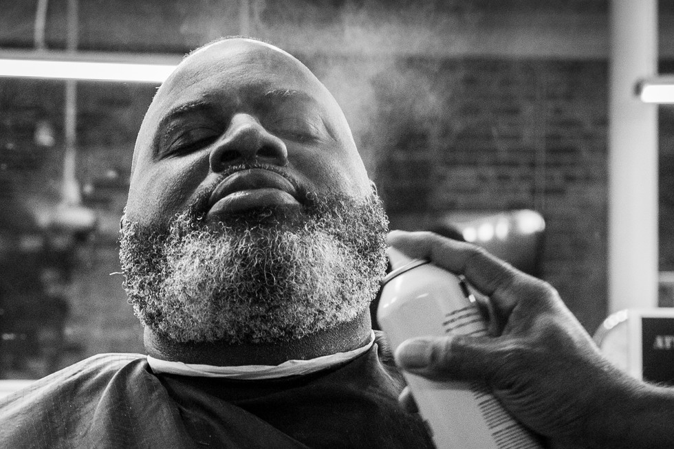 A customer receives the final touches on his beard after his hair is cut by barber Jeffery Warren on August 31. Warren hopes the barber shop can be a place for customers to relax and feel at home.