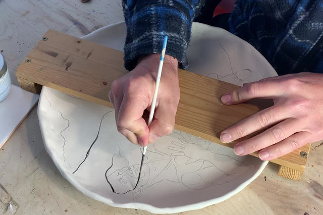 Mermen. Process of painting the mermen on ceramic platters.