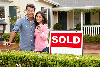 Hispanic couple outside home with sold s