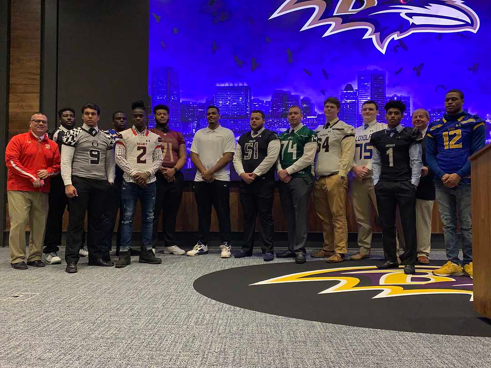 Baltimore Raven left tackle Ronnie Stanley (center, white shirt), a former 1st round draft pick, poses several members of the 2019 Team Maryland roster, who gathered for a press conference to announce the entire roster, Saturday morning at the Baltimore Ravens' Under Armour Performance Center.