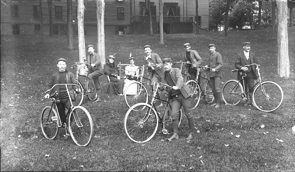 Group of seven men in cycling attire standing with their bicycles circa 1895. Two women with birds adorning their hats sit in the background. Clapboard structure with windows in the far background. From the Crandall Library Photograph Collection #CLP2164, The Folklife Center at Crandall Public Library, Glens Falls, NY.