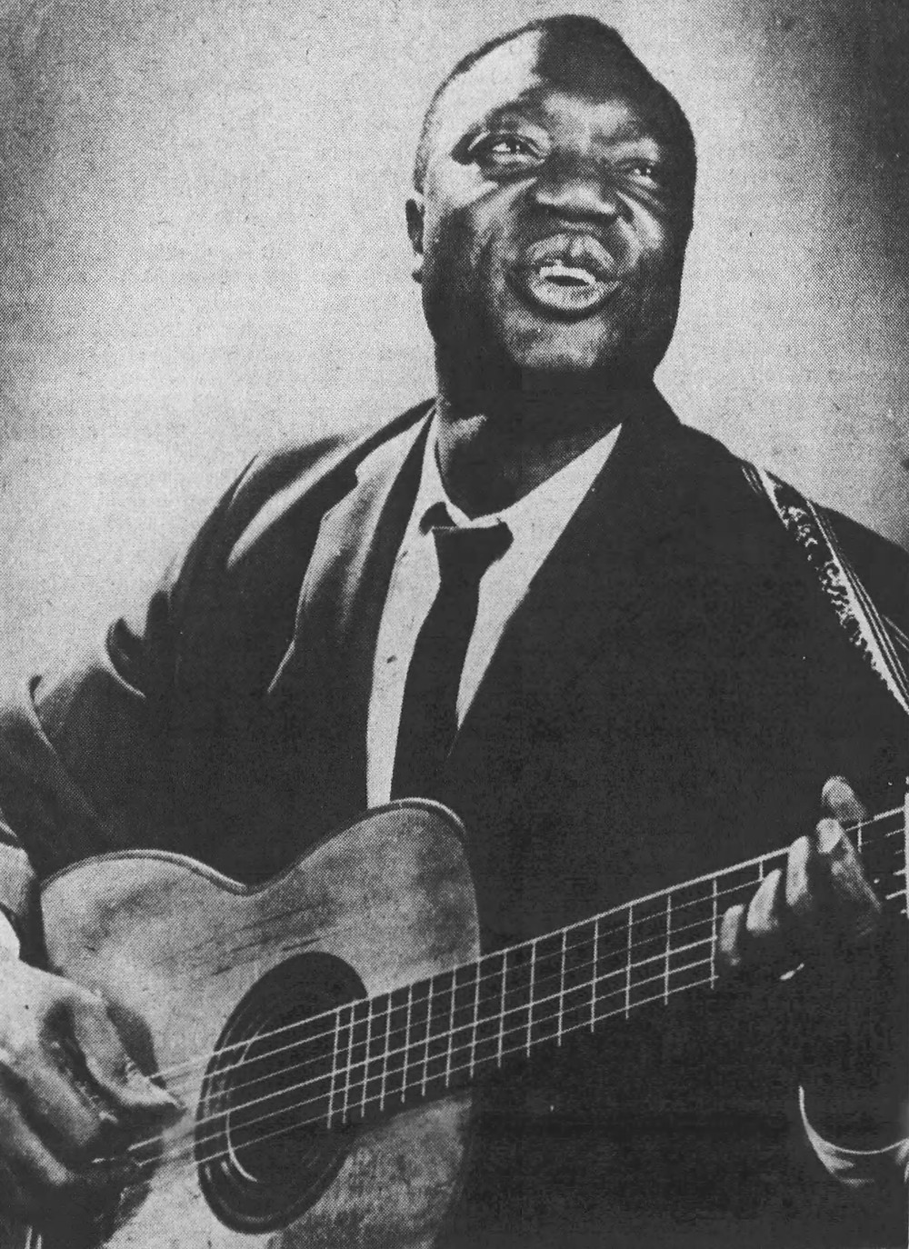 Promotional photo of Tedd Browne singing and playing guitar, circa 1965.