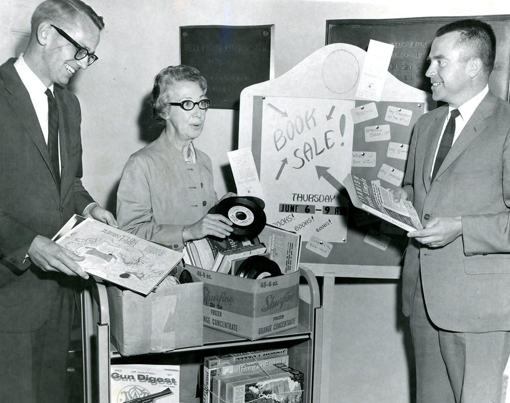 Thomas Sedgwick, Caroline Hopkins, and Richard Bergsund look at book sale items, 1968 <CLP257 Crandall Library Photograph Collection, The Folklife Center at Crandall Public Library>
