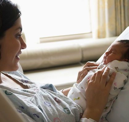 Postpartum mother admires her newborn baby shortly after birth.