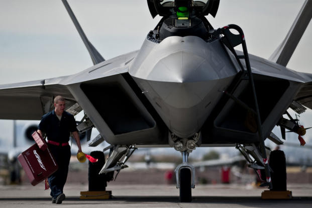 An airman removes the intake covers of an F-22 Raptor before a training mission. The first metallic 3D-printed part was installed on an operational F-22 in December at Hill AFB, Utah. (US Air Force photo/Michael Holzworth)