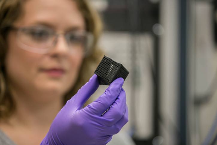 "Lab researcher Jennifer Rodriguez examines a 3D printed box that was ""programmed"" to fold and unfold when heated. (Photo by Julie Russell/LLNL)"