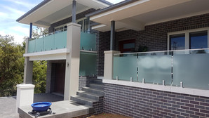 front view of black brick home with frosted glass