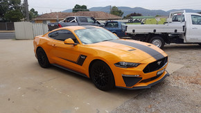 ford mustang with dark yellow wrap with black strip