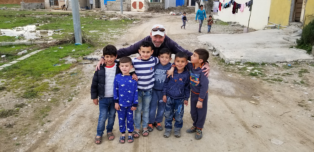 Mike Parks with young boys on a dirt road in iraq