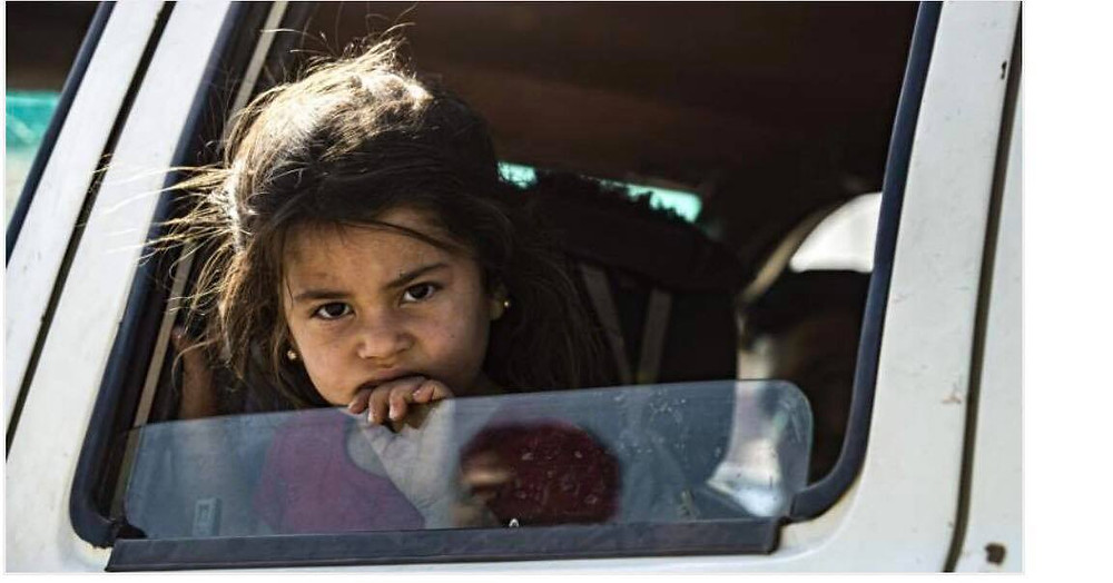 Young refugee girl looking out a car window