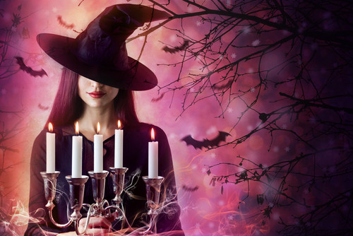 smiling witch wearing tilted black hat holding candlesticks with flying bats background